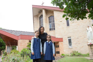 Mother and two daughters in front of St Michael's parish
