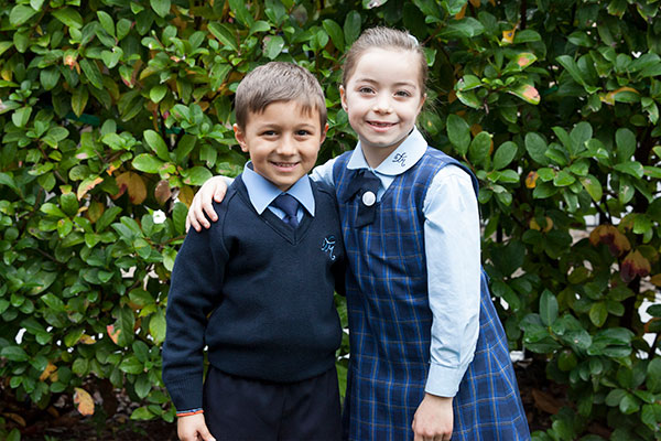 Two students at St Michael's Catholic Primary School Daceyville smiling in front of green hedge