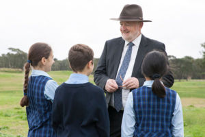 Principal Geoffrey Carey at St Michael's Catholic Primary School talking to student on a nature walk